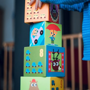 Photo of child's arms stacking large blocks with colored drawings of animals and cars