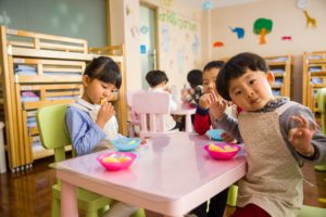 Photo of children sitting at table and eating