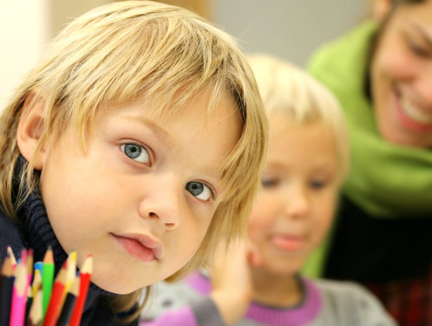 Blond boy looking at camera with another child and a teacher in background