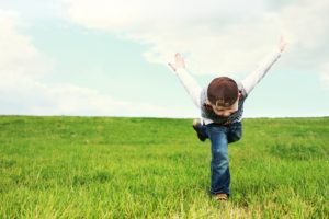 Photo of a child in a field of grass and sky above