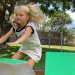 A blonde girl jumping in an outdoor tumbling class at Little Hoku