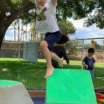 A boy jumping in an outdoor tumbling class at Little Hoku
