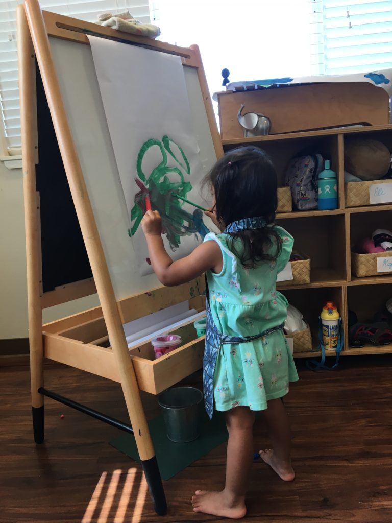 Little Hoku female student drawing holiday related drawings at easel