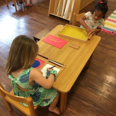 Two children working together on classroom activity at a table