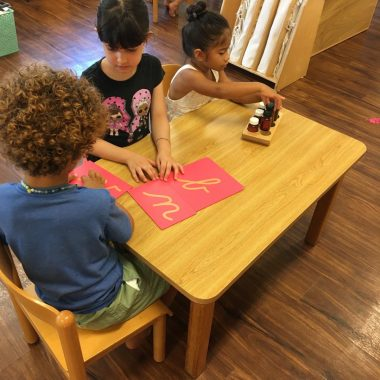 Three children working together on classroom activity at a table