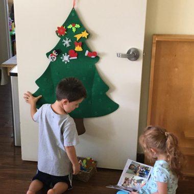Children decorating Christmas tree on door