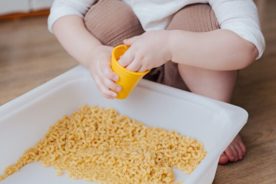 Child playing with dry macaroni