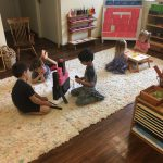 Four Little Hoku students sitting on a rug doing math activities