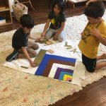 Four Little Hoku students sitting on a rug doing math activities with shapes